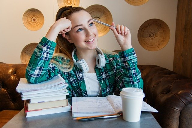 college girl with books and a coffee smiling