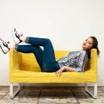 girl laying on a yellow sofa